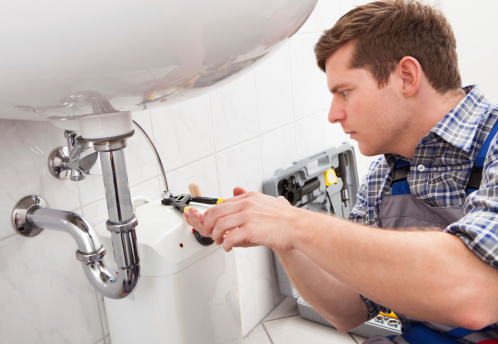 plumber fixing a sink in bathroom